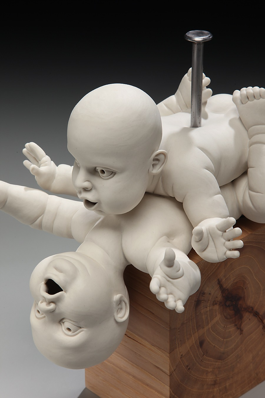 """RUSSELL BILES;""""Nailed (Babies Making Babies)""""; 2010; hand built porcelain, wood;h8""""; photo Tim Barnwell."""